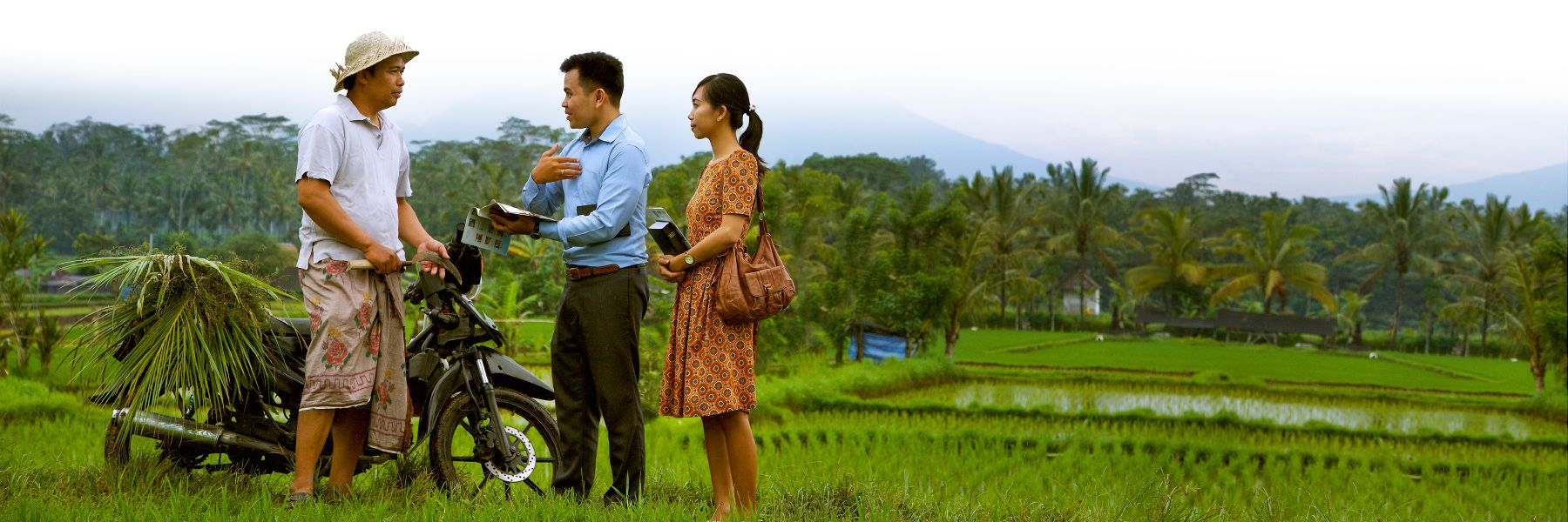Two of Jehovah's Witnesses preaching to a man in a rice paddy.