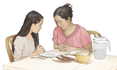 A mother says a prayer with her daughter before they eat a meal