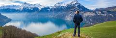 Человек смотрит, как в озере отражаются горы со снежными вершинами