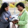 Jehovova svedkyňa číta domácej panej z Biblie