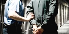 Një i burgosur me pranga duke e çuar në qeli