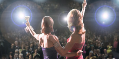 Two actresses in front of a crowd