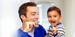 A father and his young son brushing their teeth
