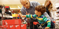 A little boy is reaching for a toy on a store shelf and his father is saying no