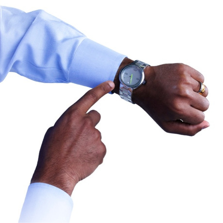 Um homem aponta para seu relógio de pulso