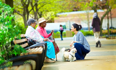 Carol and Mildred sharing good news from the Bible with a passerby in a park
