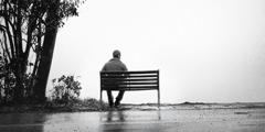 En mann som sitter på en benk