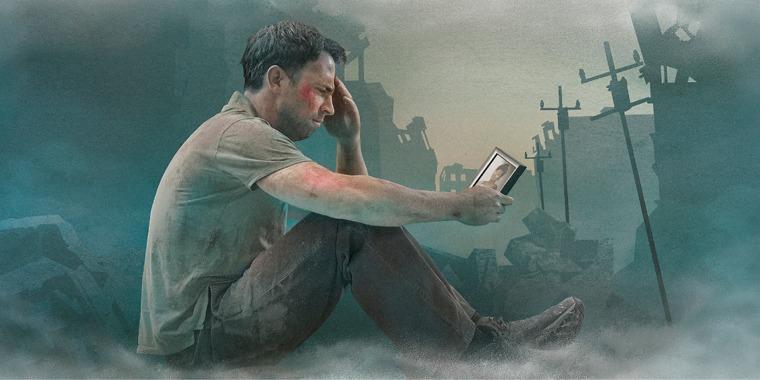 Um homem com problemas olha uma foto enquanto está sentado sobre escombros