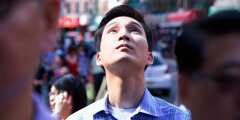A man looks toward the heavens while others go about their daily activities