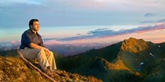 A man sits and looks out at a mountain range and beautiful sky