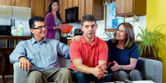 A husband sits uncomfortably between his in-laws while his wife notices from behind