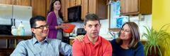 Mož neudobno sedi med tastom in taščo, žena pa v ozadju opazuje.