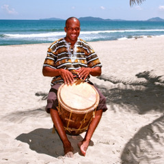En man från garífunafolket spelar på en trätrumma.