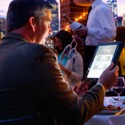 A man dining at a restaurant uses an electronic device