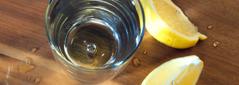コップに入った清潔な水と,くし形切りにしたレモン