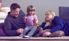 En mamma och pappa sitter på golvet med sin lilla dotter