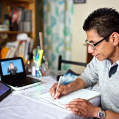 Daniel, ki je gluh, si dela zapiske, medtem ko se v ozadju predvaja DVD v mehiškem znakovnem jeziku.