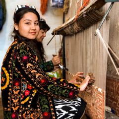 Två uzbekiska kvinnor tillverkar sidenmattor