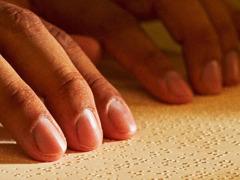 Una persona legge la Torre di Guardia in braille