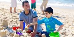 En far og sønnen hans koser seg sammen på stranden