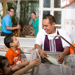 Josué washes dishes while he enjoys the company of a young family
