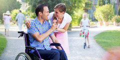 A man in a wheelchair gives his wife a flower