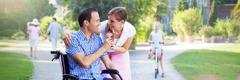 Мъж в инвалидна количка подарява цвете на жена си