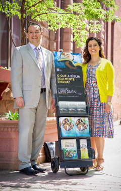 Two of Jehovah's Witnesses use a mobile display cart in the public ministry