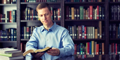 In a library full of books, a man chooses to read the Bible