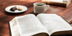 Biblía liggur opin við hliðina á kaffibolla.