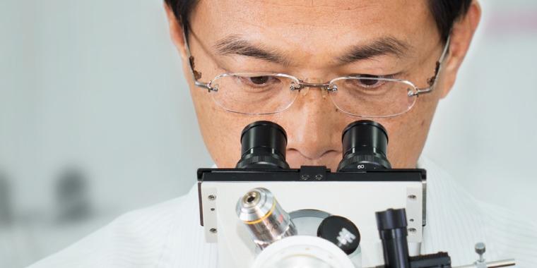 Yan-Der Hsuuw looks into a microscope