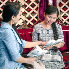 One of Jehovah's Witnesses studies the Bible with a woman in Kyrgyzstan