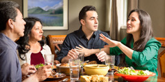 A wife interrupts her husband during dinner with another couple