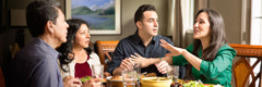 Zwei Ehepaare beim Abendessen; eine Frau fällt ihrem Mann ins Wort