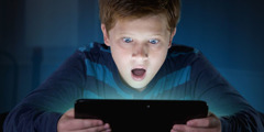 A boy is astonished by what he sees on his electronic device