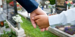 A child holds an adult's hand in a cemetery