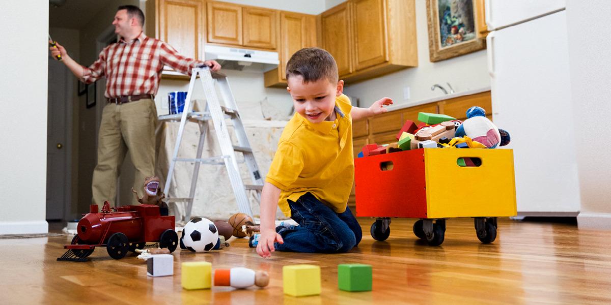 Un niño pequeño recoge los juguetes mientras su padre pinta la pared de la cocina