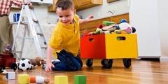 En pojke plockar ihop sina leksaker och hans pappa målar köksväggen