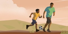 A man plays soccer with his son