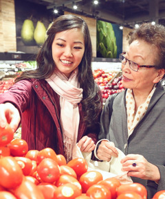 A young woman helps an older woman with her grocery shopping