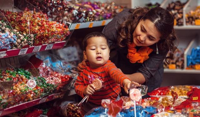 Un niño intentando tomar un caramelo de una tienda y su madre diciéndole que no
