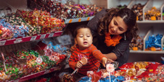 A mother says no as her little boy tries to pick out candy in a store