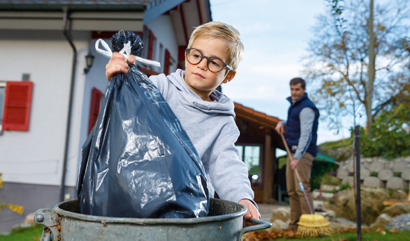 Um menino jogando o lixo fora
