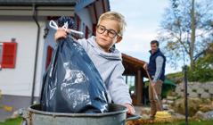 Chlapec vyhazuje pytel s odpadky do popelnice