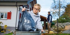 A boy puts trash in a bin