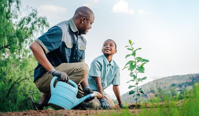 Un padre ayudando a su hijo a regar una planta