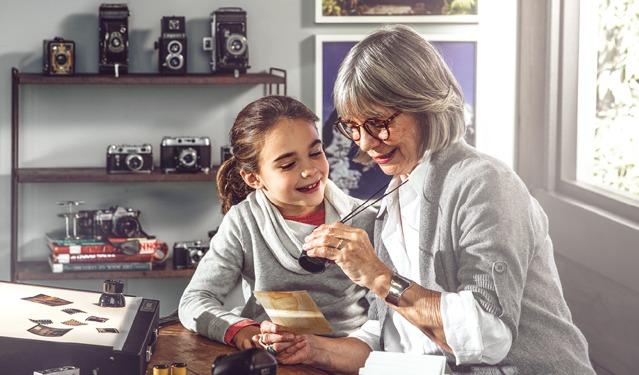 Una mujer enseñándole a una niña sus fotos antiguas