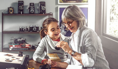 Une femme montre ses vieilles photos à une petite fille