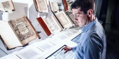 Čovjek gleda stare Biblije u muzeju