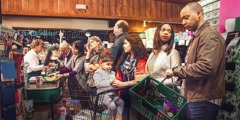 People are agitated in a checkout line at a grocery store, but one woman and her little girl remain calm